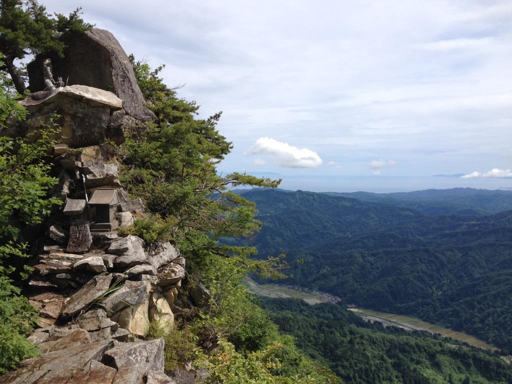 白山権現の石祠と直下の須川集落、松の枝の上には佐渡も見えるよ
